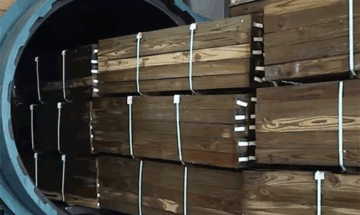 treated lumber coming out of cylinder